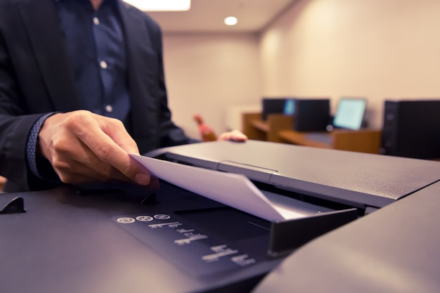 クローズアップショットビジネスマンは、コピー機のトレイに紙を置きます。