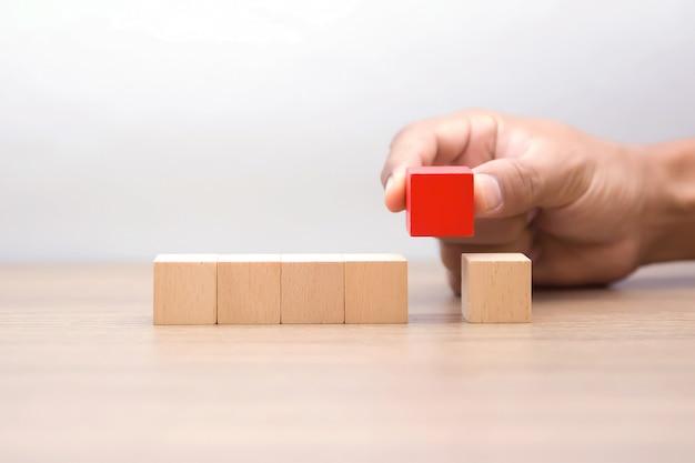 Рука, выбирая деревянный блок без графики.
