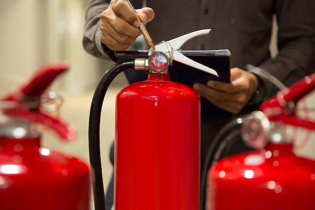 エンジニアは消火器をチェックしています。