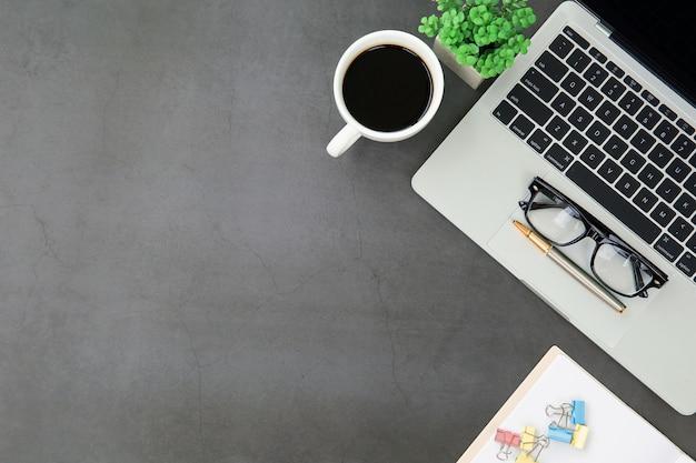 ラップトップコンピューターとコーヒーカップ付きのトップビューデスク