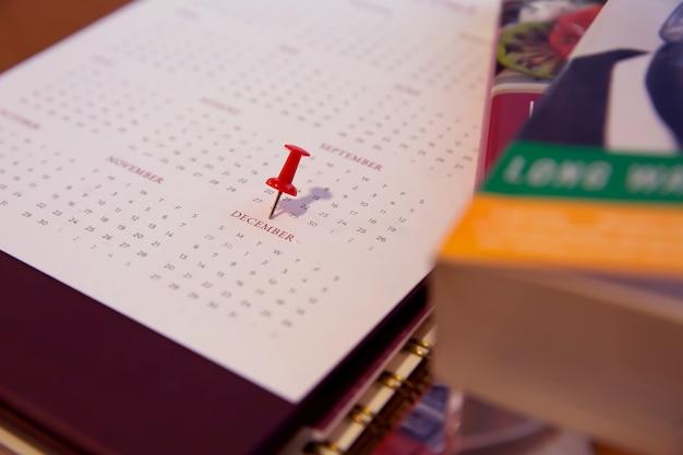 Красная булавка с календарем на декабрь