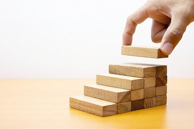 Рука ставит деревянные кусочки.