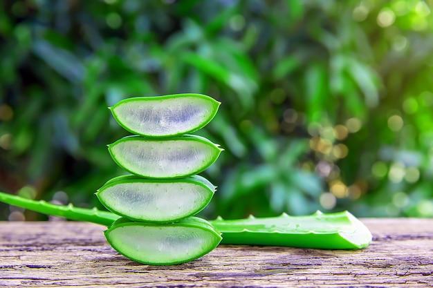 新鮮なアロエベラの葉と木製のテーブルのスライス。