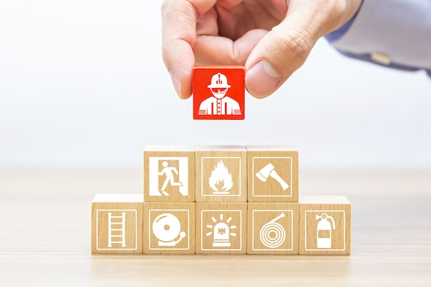 Рука выбрать деревянный блок с иконой пожарного.
