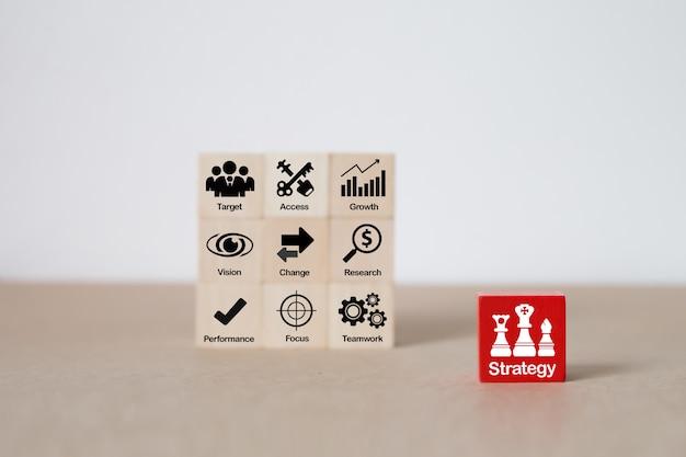 Значки стратегии на деревянном блоке для роста бизнеса.