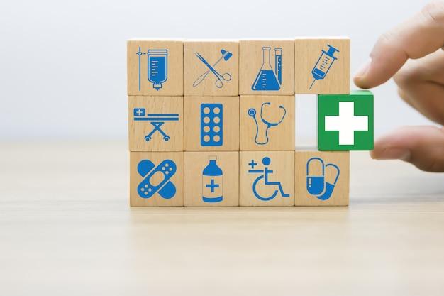 手は木製のブロックの医療と健康のアイコンを選択します。