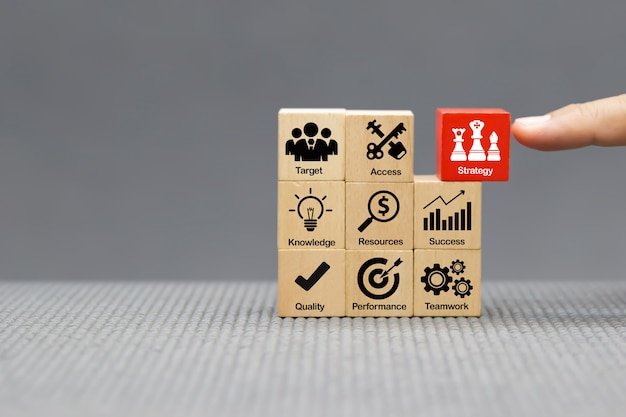 Значки стратегии на деревянном блоке для успеха, производительности, управления и роста бизнеса.