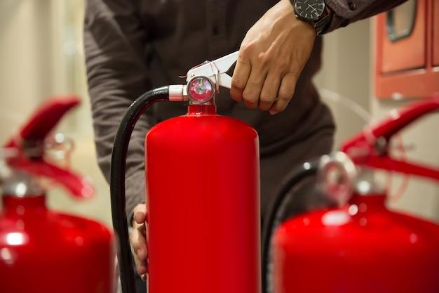 クローズアップエンジニアの手は、消火器のハンドルを絞っています。