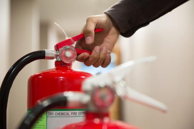 エンジニアの手が消火器のハンドルを握り締めています。