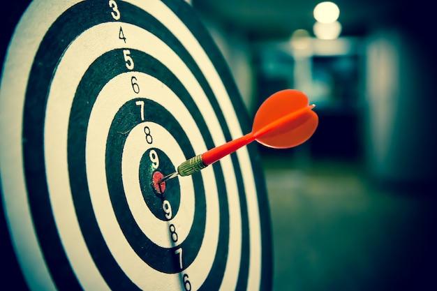 雄牛の目のターゲットの中心を打つ赤いダーツの矢。