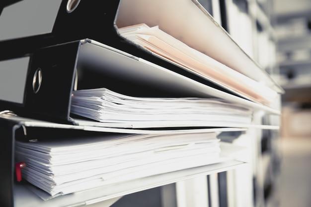 ファイル保管室の棚に積み重ねられたドキュメントフォルダー。