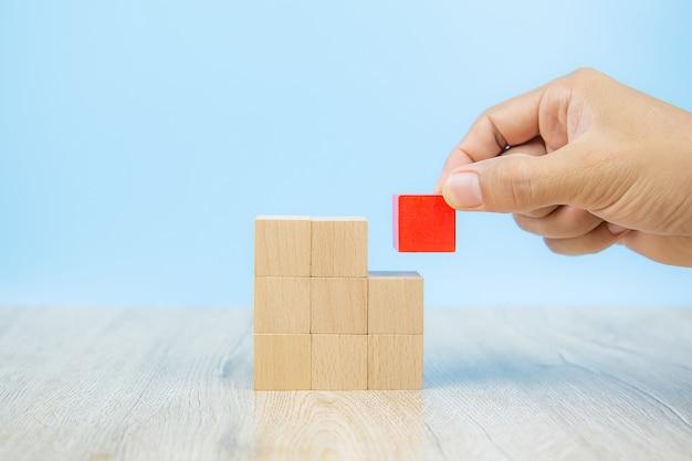 Рука крупного плана выбирает игрушку деревянного блока кубической формы сложенную без графики.