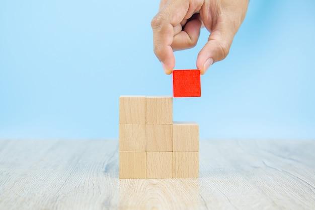 クローズアップの手は、グラフィックなしで積み上げられた立方体の形の木製のブロックのおもちゃを選択します。