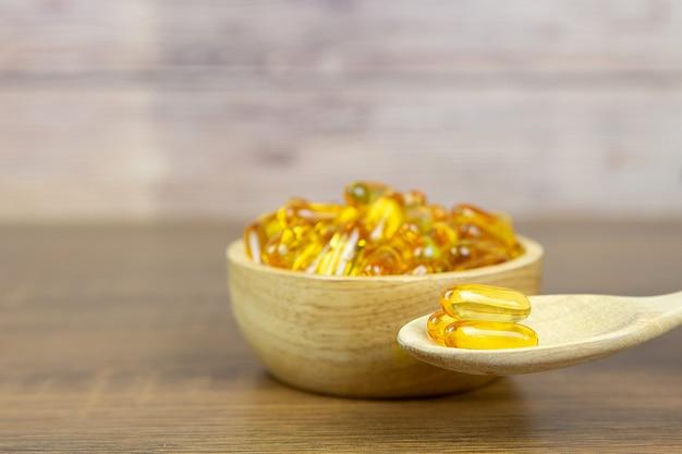Куча капсулы масла печени трески в чашке и деревянной ложке.