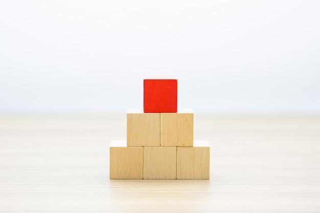 Игрушка из кубика в форме деревянного блока, сложенная в форме пирамиды без рисунка.