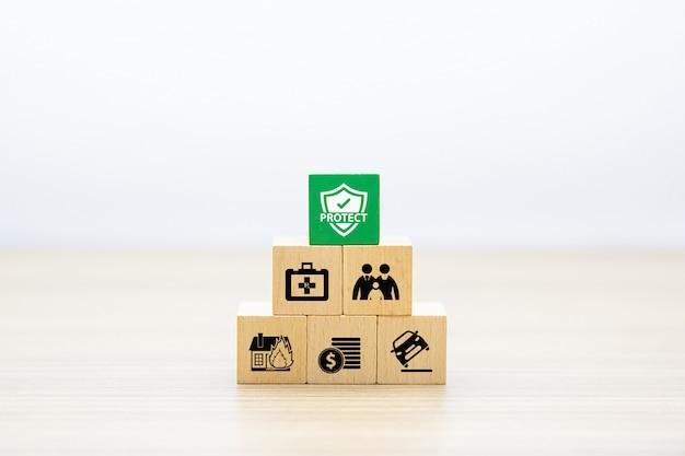 保険のアイコンが付いたピラミッド型に積み上げられた木のおもちゃブロック。