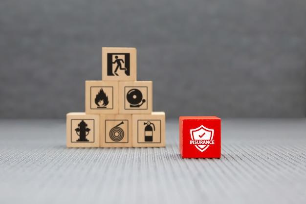 火災安全保護のための保護アイコンが付いている木のおもちゃのブロック。