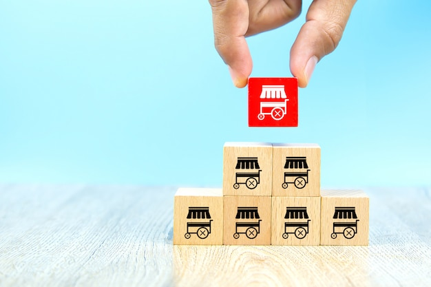 Рука бизнесмена выбирает блог игрушки красного цвета деревянный штабелированный с магазином значков маркетинга франшизы.