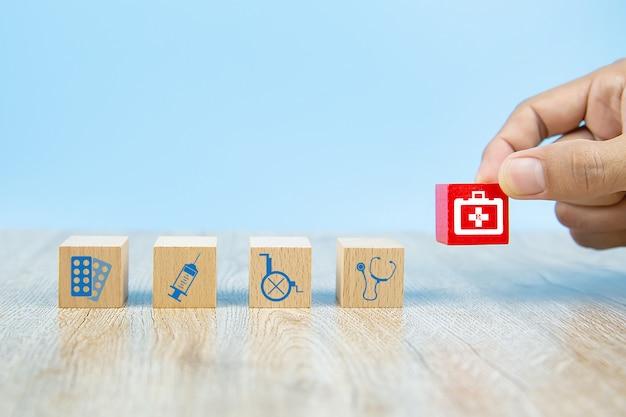 クローズアップ手は木のおもちゃのブロックにヘルスケアと医療のシンボルアイコンを選択します。