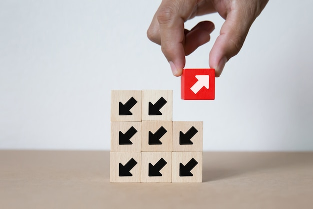 木のおもちゃブロックの赤い矢印記号を選ぶ手。