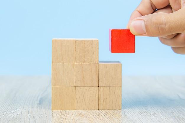 クローズアップの手は、ビジネスデザインコンセプトのグラフィックスなしで積み上げられた、立方体の形の木製のブロックのおもちゃと、子供の基礎練習スキルのアクティビティを選択します。