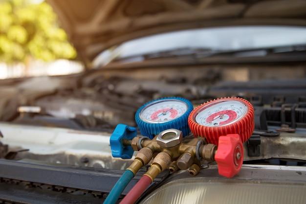 カーエアコン充填確認用測定器。車の修理サービスと自動車保険の概念。