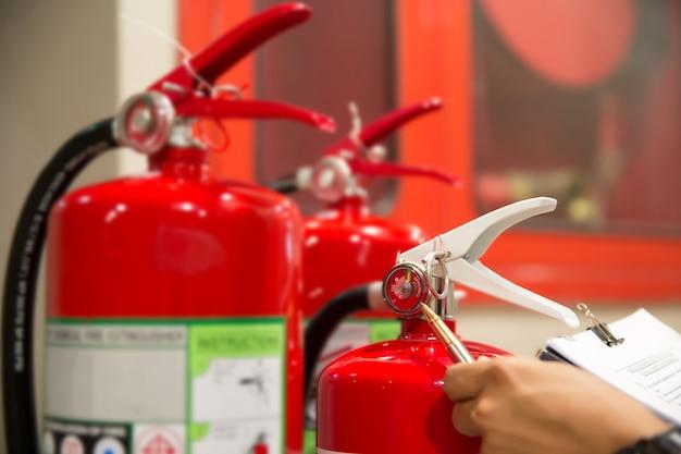 エンジニアは消火器を点検しています。