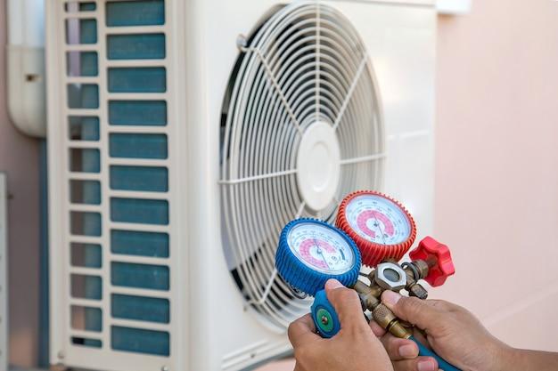 エアコンを充填するための測定機器を使用し、屋外の空気圧縮機ユニットをチェックする技術者。