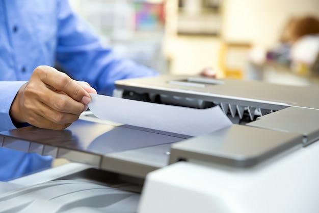 Бизнесмены загружают бумагу в копир и используют копировальный аппарат или принтер для распечатки, сканирования, выписки документов в офисе.