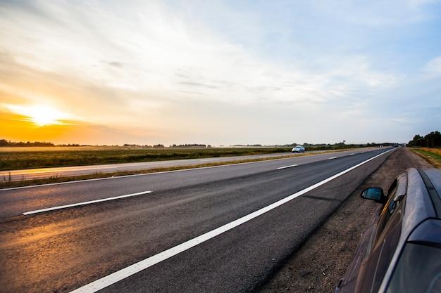 美しい夕日の田舎のアスファルト道路ビュー。