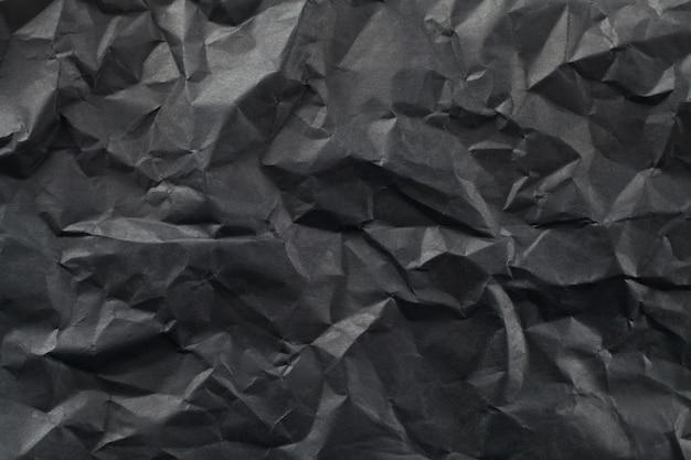 黒い紙のしわシートの背景。