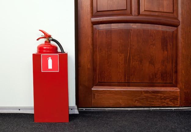 Огнетушитель рядом с пожарным выходом.