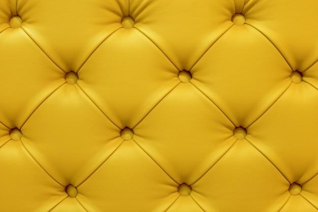 黄色の革のソファ、ステッチボタンの背景。