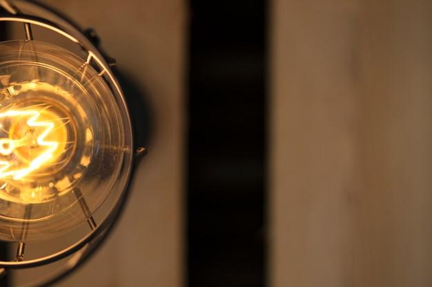 木製の屋根の上に中断金属シェードのヴィンテージエジソン電球。