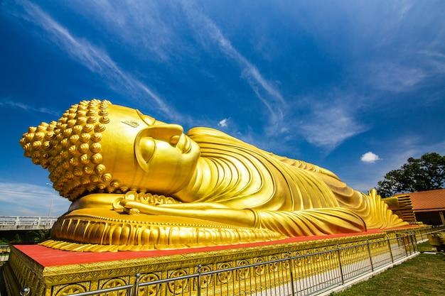 Статуя будды спящего персонажа с золотистым цветом