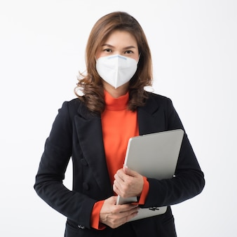 スーツのビジネスウーマンはコンピューターを保持し、マスクを使用してコロナウイルスから保護します