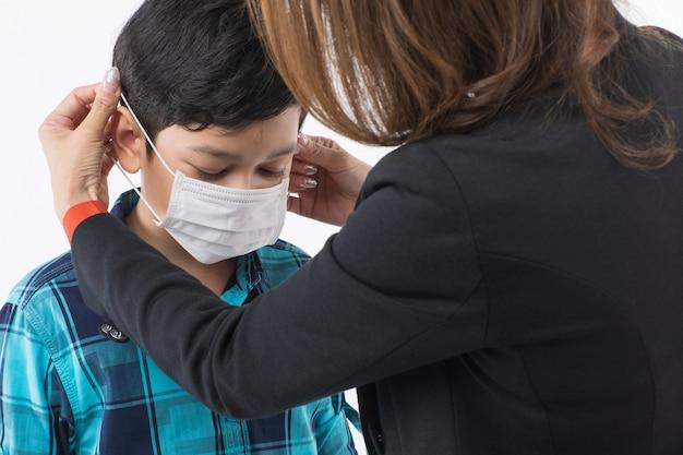 母親は息子のサージカルマスクを着ています。