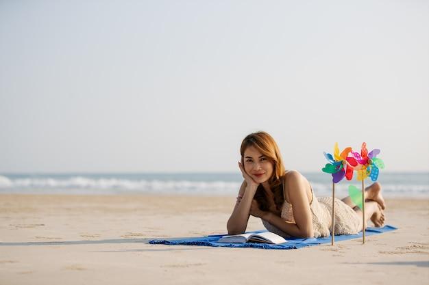 アジアの女性はビーチに敷設と読書