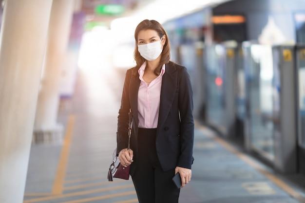 電車を待っているマスクを身に着けている女性実業家。