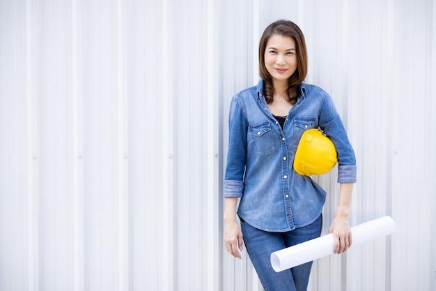 Азиатский женский инженер с желтой трудной шляпой.