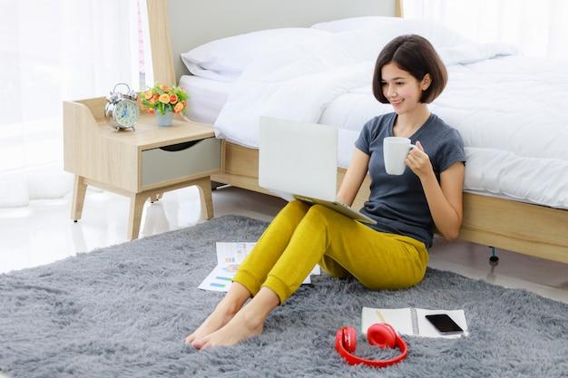 座っていると寝室でコンピューターを使用している女性