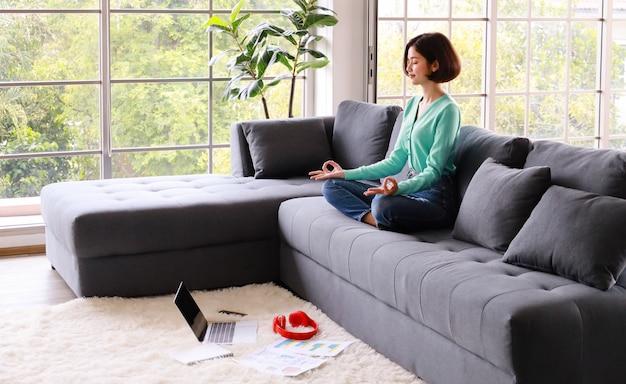 ソファに座って瞑想をしている若い美しい