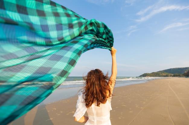 ビーチでウェイバー布を持つ女性