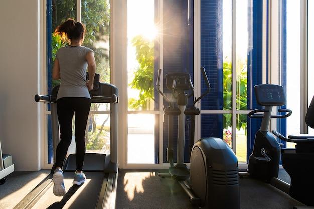 トレッドミル運動器具のフィットネスジムで走っている女性。