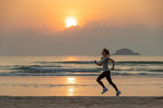 日の出でビーチを走る女性