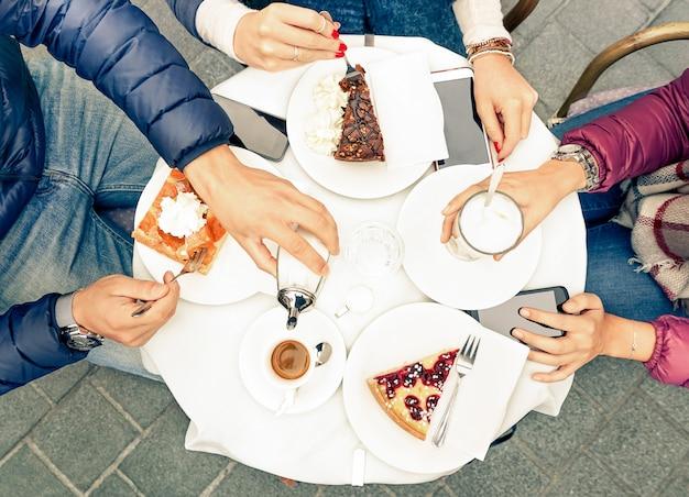 Группа друзей с пирожными кофе и молоком в баре-ресторане