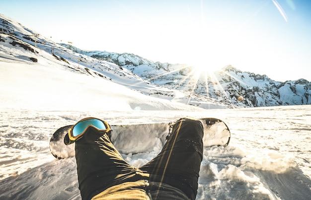 Сноубордист, сидя на закате на расслабляющий момент в европейских горнолыжных курортах альп
