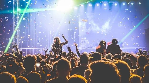 Молодые люди танцуют в ночном клубе на концертном фестивале