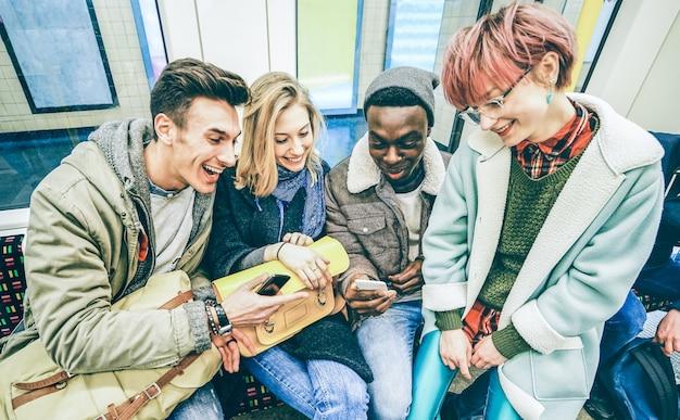 地下鉄の電車で楽しんでいる多民族のヒップスターの友人のグループ
