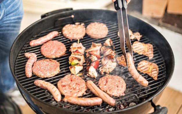 バーベキューセッションで肉を焼く手のクローズアップ